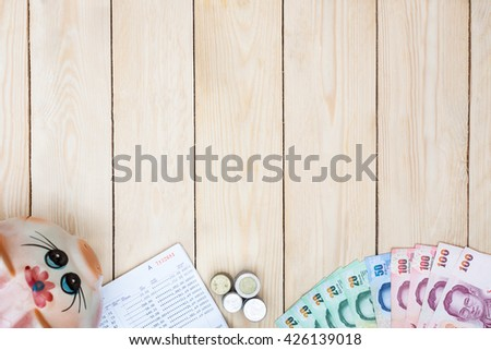 Blank space with money and saving account passbook, Book bank statement in the middle of office equipment on office desk. Finance wooden background. Top view. - stock photo