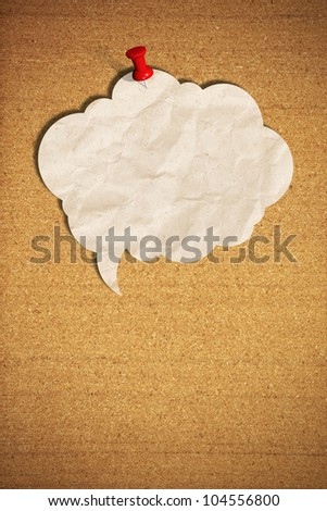 blank speech bubble note paper with push pins on cork board - stock photo