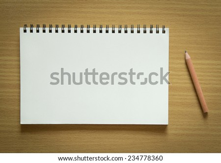 blank spiral notebook and pencil on wood background - stock photo