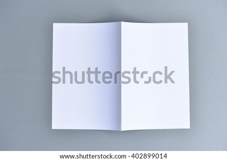 Blank square brochure, A4 half folded, inside facing down, isolated on grey cardboard background, with clipping path included, changeable background. For several printing matters and creative designs. - stock photo