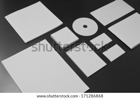 Blank stationery set on black wood background / a4 paper, business cards, letterheads, disk, envelope, booklet, notepad - stock photo