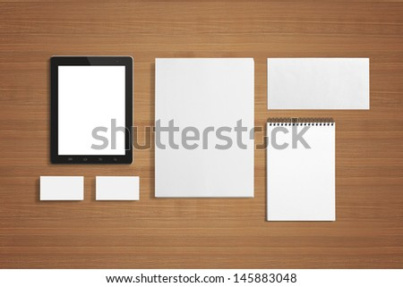 Blank Stationery set on the wooden background with soft shadows. Consist of Business cards, A4 letterheads, Notebook, Tablet PC and Envelopes. - stock photo