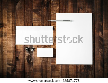 Blank stationery set on vintage wooden table background. ID template. Mockup for branding identity for designers. Blank letterhead, business card, envelope and pen. Top view. - stock photo