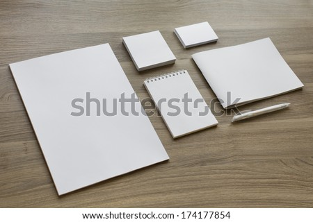 Blank stationery set on wood background / a4 paper, business cards, letterheads, booklet, notepad and pen - stock photo