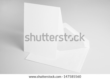 Blank stationery: standing card and envelope over grey background with shadow - stock photo