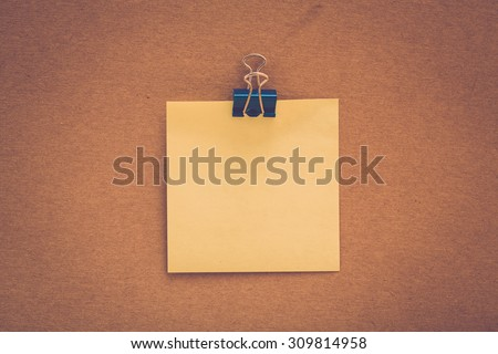 Blank sticky note on brown paper with paper clip. Retro filter - stock photo