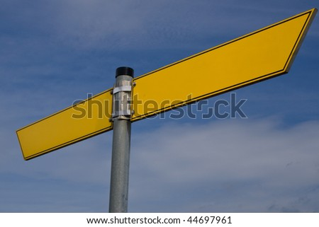 Blank street sign arrows in yellow before blue sky