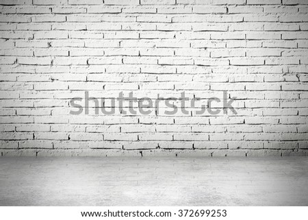 Blank stucco interior in dark light with brick wall