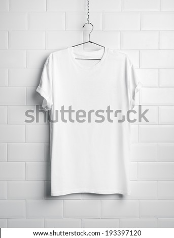Blank t-shirt hanging on white wall - stock photo