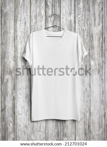 Blank t-shirt on wood wall - stock photo