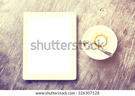 Blank tablet and cappuccino on a wooden table, mock up - stock photo
