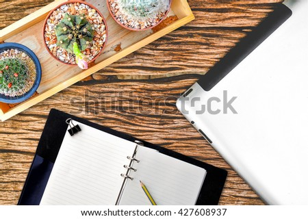 blank tablet and phone with an empty folder on a wooden workspace