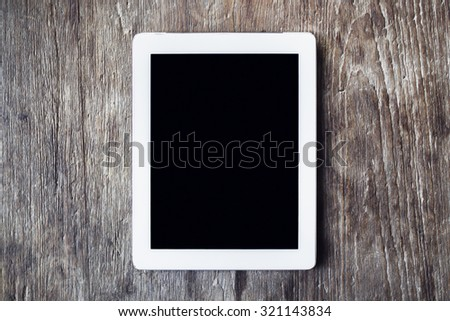 Blank tablet on a wooden table - stock photo