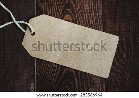 Blank tag on dark wood background - stock photo