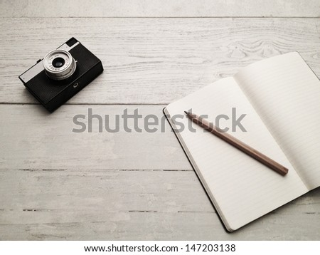 Blank textbook and vintage analog camera on white hardwood desk. Shot with smart phone. - stock photo