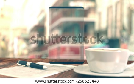 Blank transparent glass screen, coffee cup, notepad and pen on city background with vintage colouring. - stock photo