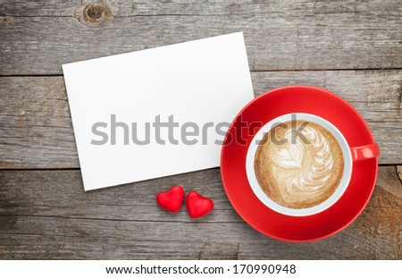 Blank valentines greeting card and red coffee cup on wooden background - stock photo