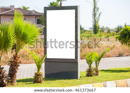 Blank vertical billboard on the streets . Near palm trees and beautiful nature