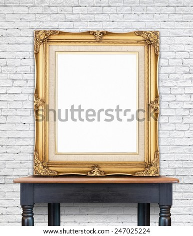 Blank vintage golden photo frame lean at white brick  wall on wood table,Template Mock up for add picture. - stock photo
