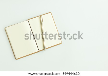 blank vintage notebook paper and gold pen on white background