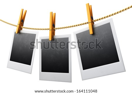 Blank vintage photo frames hanging on a clothesline isolated on white - stock photo