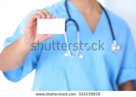 Blank visiting card in  unknown male surgeon doctor hand - stock photo