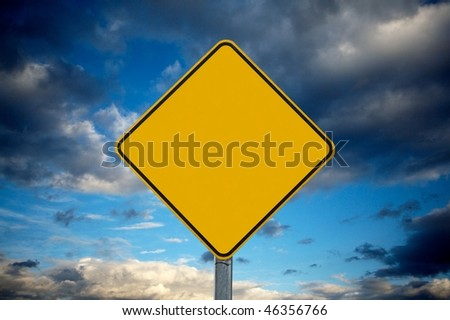 Blank warning traffic sign against cloudy sky