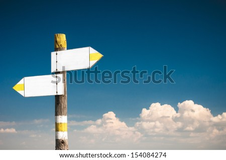 Blank white arrow road sign at the blue sky - stock photo