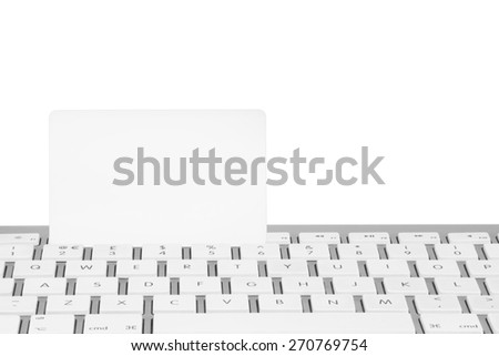 Blank white bank card  on a computer keyboard with a white background - stock photo