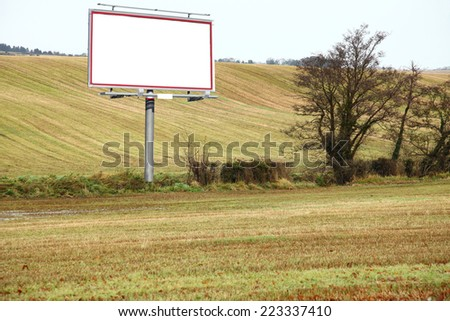 Blank white billboard in field with space for your advertisement - stock photo