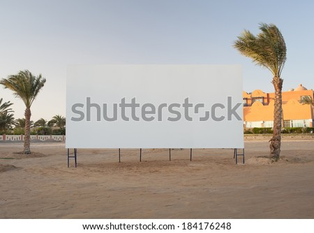 Blank white billboard with copyspace for your advertisement or movie flanked by two palm trees - stock photo