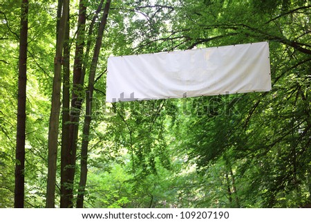 Blank white board banner and green trees - stock photo