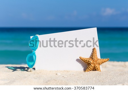Blank white board, swimming glasses and starfish on sand against turquoise caribbean sea water. Tropical summer vacation concept - stock photo