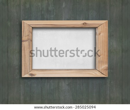 Blank white board with wooden frame on old green wood wall - stock photo