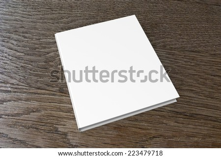 Blank white  book cover isolated on the wooden background - stock photo