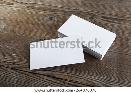 Blank white business cards on a dark wooden background. Mockup for branding identity. Shallow depth of field. - stock photo