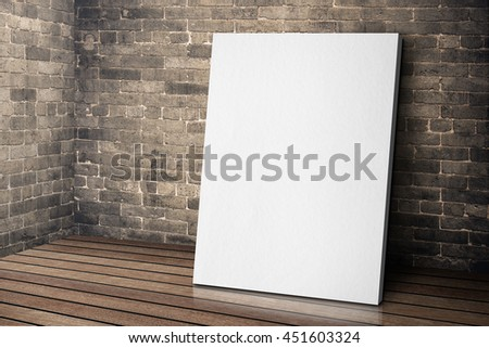 Blank white canvas frame leaning at grunge brick wall and wood f