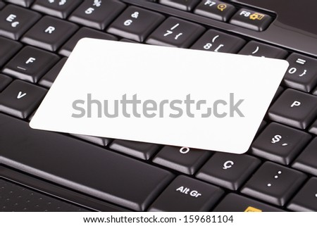 Blank, white card on black computer keyboard buttons. - stock photo