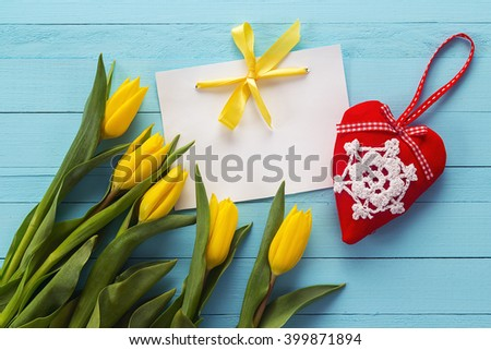 Blank white card with yellow tulips and red heart on blue painted wooden planks. Place for text. Top view with copy space - stock photo