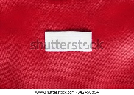 Blank white clothes label on red silk