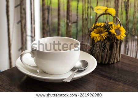 Blank white cup with a teaspoon on the table in a cafe