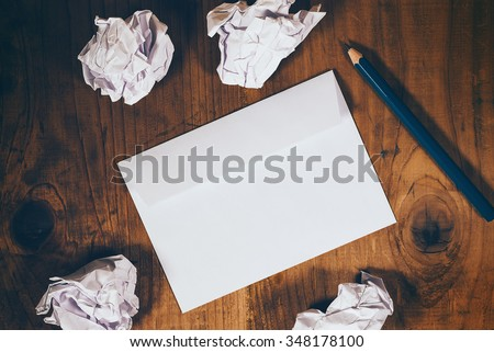 Blank white envelope, pencil and crumpled paper on wooden office desk, retro toned, top view - stock photo