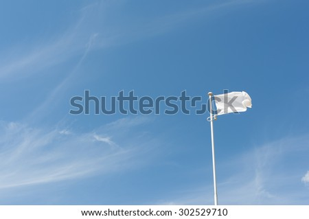 Blank white flying flag on a blue sky - stock photo