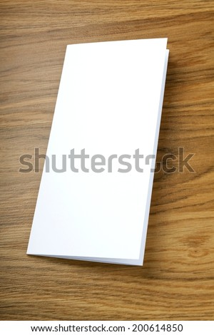 blank white folding paper flyer on a wooden background, identity design, corporate templates, company style - stock photo