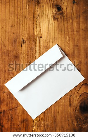 Blank white mailing envelope on office desk, copy space, top view - stock photo