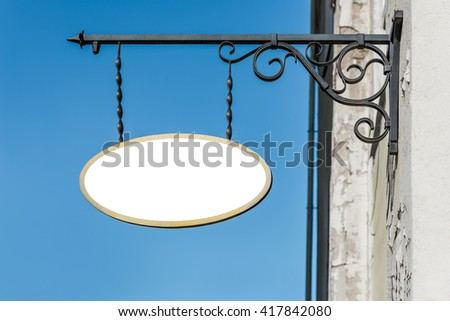 Blank white mock up of shop vintage metal signboard on blue sky background