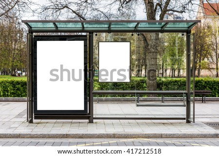 Blank white mock up of vertical billboard in a bus stop - stock photo