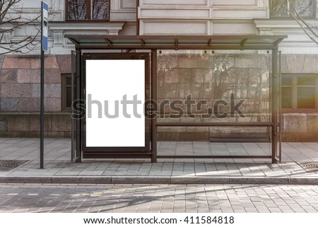 Blank white mockup of bus stop vertical billboard in empty street - stock photo