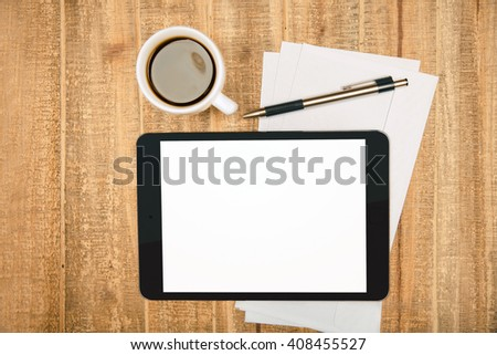 Blank white pad screen on wooden table with coffee, paper sheets and pen. Topview, Mock up