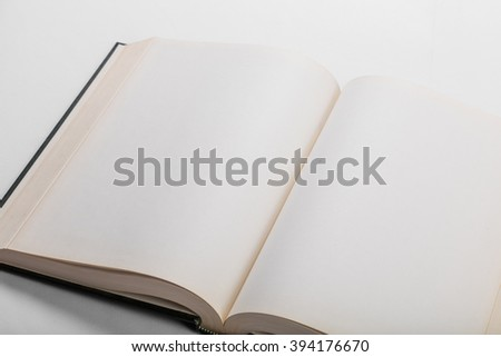 Blank white pages in an open hardcover book. - stock photo